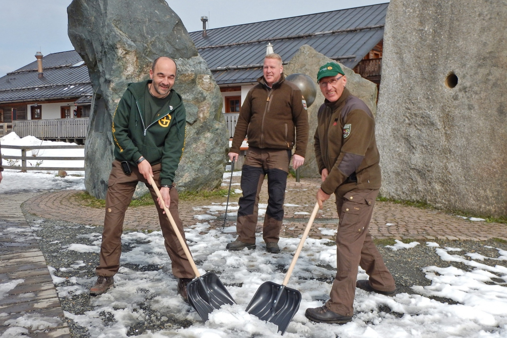 Markus Gründel und zwei Nationalpark-Ranger stehen mit Schaufeln und Müll-Sammelgreifer vor den Felsen des Nationalpark-Monuments am Nationalpark-Besucherzentrum TorfHaus